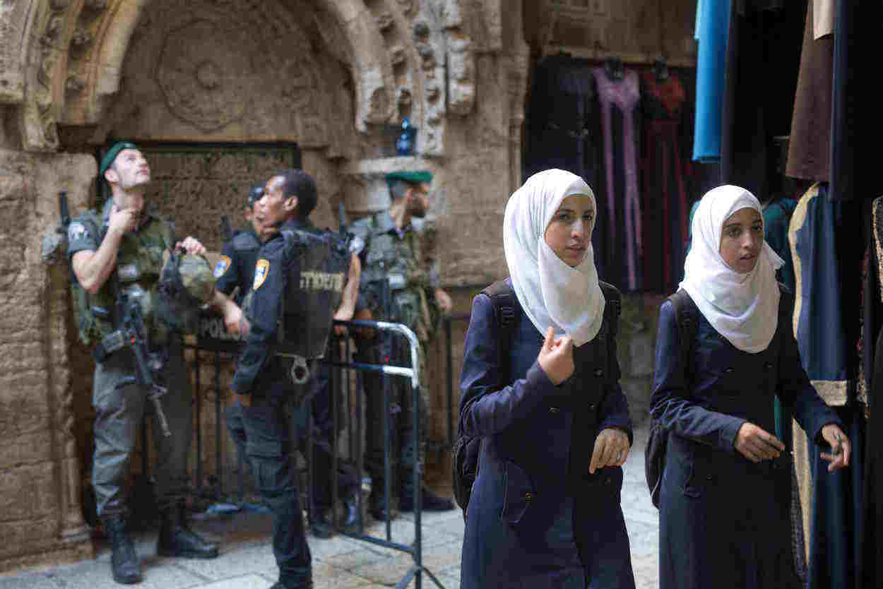 Palestinian women walk past an Israeli police checkpoint in Jerusalem's old city on October 8, 2015, under Israeli police presence due to high tension following a series of knife attacks by Palestinians on Israelis in recent days as rioting has spread across east Jerusalem and the occupied West Bank. AFP PHOTO/MENAHEM KAHANA        (Photo credit should read MENAHEM KAHANA/AFP/Getty Images)
