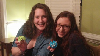 Grace Sanger-Johnson (left) and Jess Bender of Tovah BBG show off their cupcake designs during an Ultimate Game Show event hosted by their BBYO chapter.
