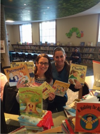 Moorestown Children's Librarian Jennifer Dunne (left) and Michelle Litwick of the Moorestown Jewish Association hold some of the many Jewish children's books recently donated to beef up the Jewish selections at the Moorestown Library.